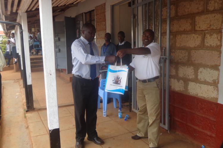 Mr Paul Kariuki - presenting a gift